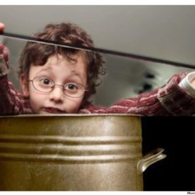 Child sitting in a large pot.