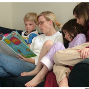 Mother reading to 4 children.