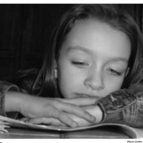 Young girl, looking bored. Arms across the textbook in front of her, and chin resting on her hands.