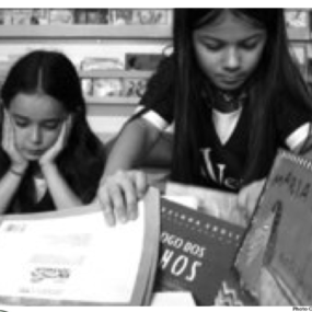Two children looking through a pile of books. Neither very excited.